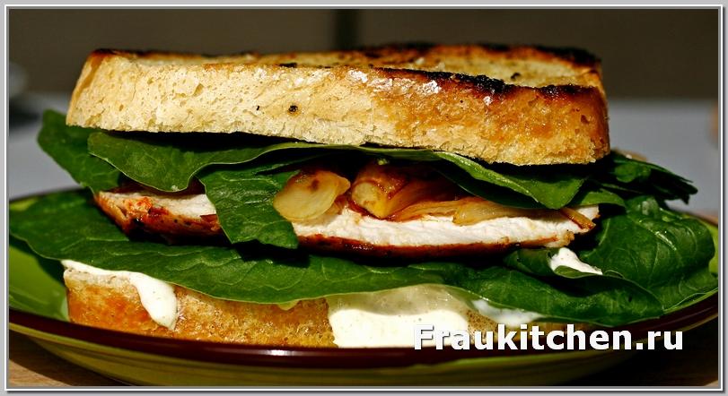 Сэндвич с курицей, соусом из сыра, хрена и майонеза, хрустящим шпинатом и сладким жареным луком.